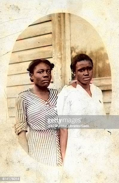 Three quarter length oval portrait of two young African American women standing in front of a house the one on the left in a striped dress the other...