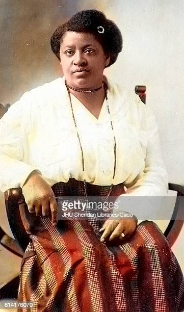 Three quarter length seated portrait mature African American women wearing dark skirt with patterns light blouse necklaces and hairpin neutral...