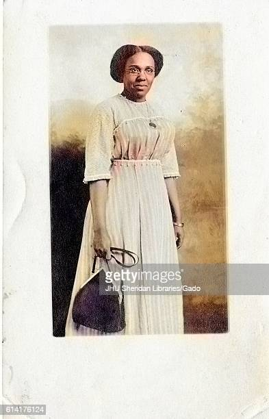 Three quarter length standing portrait of mature African American woman neutral expression carrying a purse wearing a necklace bracelet and a light...