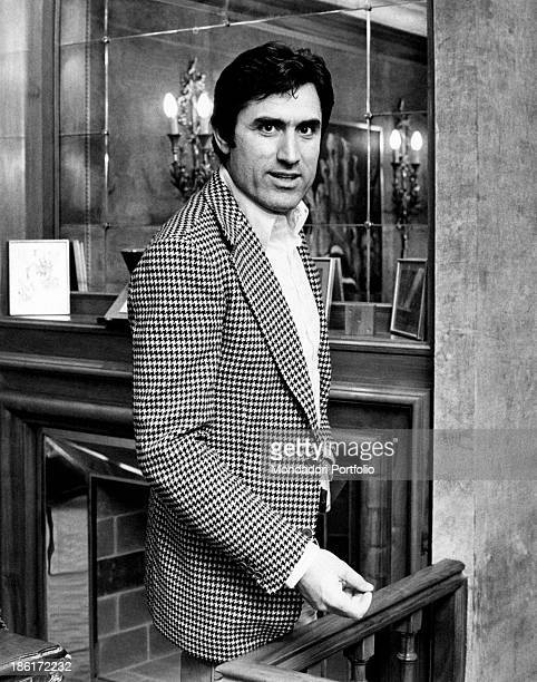 Three quarter portrait of the Italian actor Lando Buzzanca wearing a pied de poule pattern jacket and standing in front of a fireplace with a large...