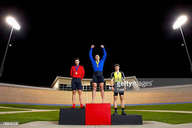 Three Racing Cyclists on Winner's Podium
