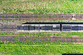Three railway tracks and in the center locomotive, top aerial view