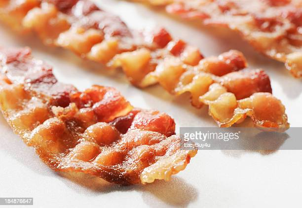 Three rashers of crispy sliced bacon on a white background