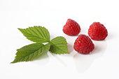 Three raspberries and raspberry leaf.