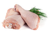 Three raw chicken drumsticks with a sprig of dill isolated on white background.