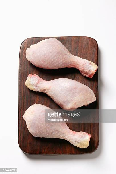Three raw chicken legs on chopping board