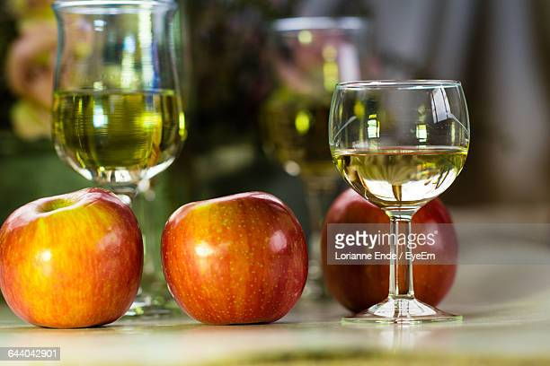 Three Red Apples And Glass Of Apple Juice On Wood