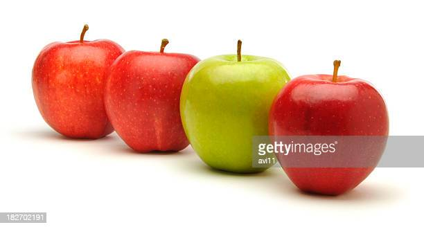 Three red apples with one green against a white background