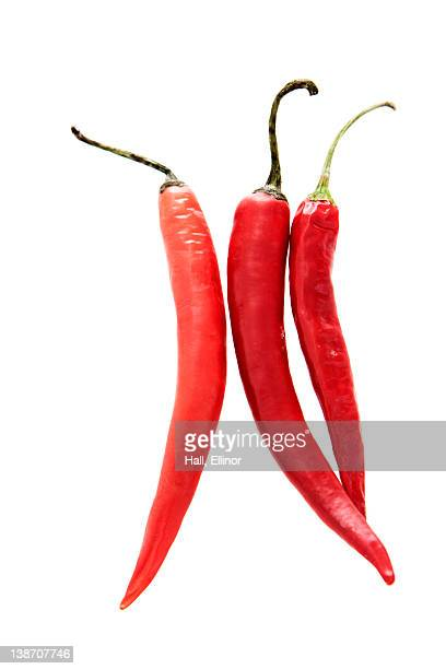 Three red chillies against white background, close-up