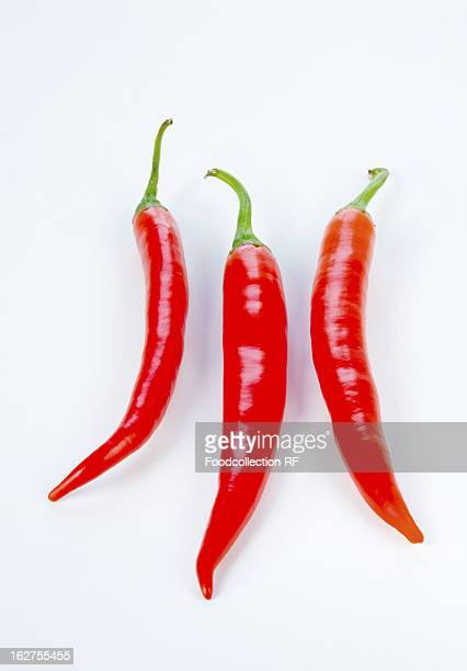 Three red chillies against white background