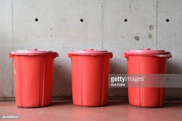 Three red dustbins