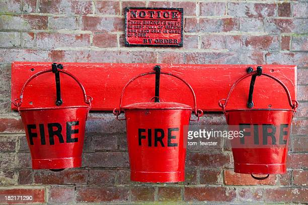 Three red fire buckets on wall
