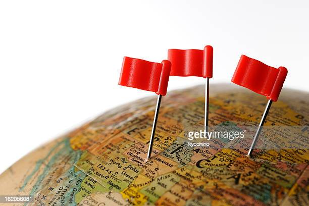 Three red flag pushpin on globe against white background