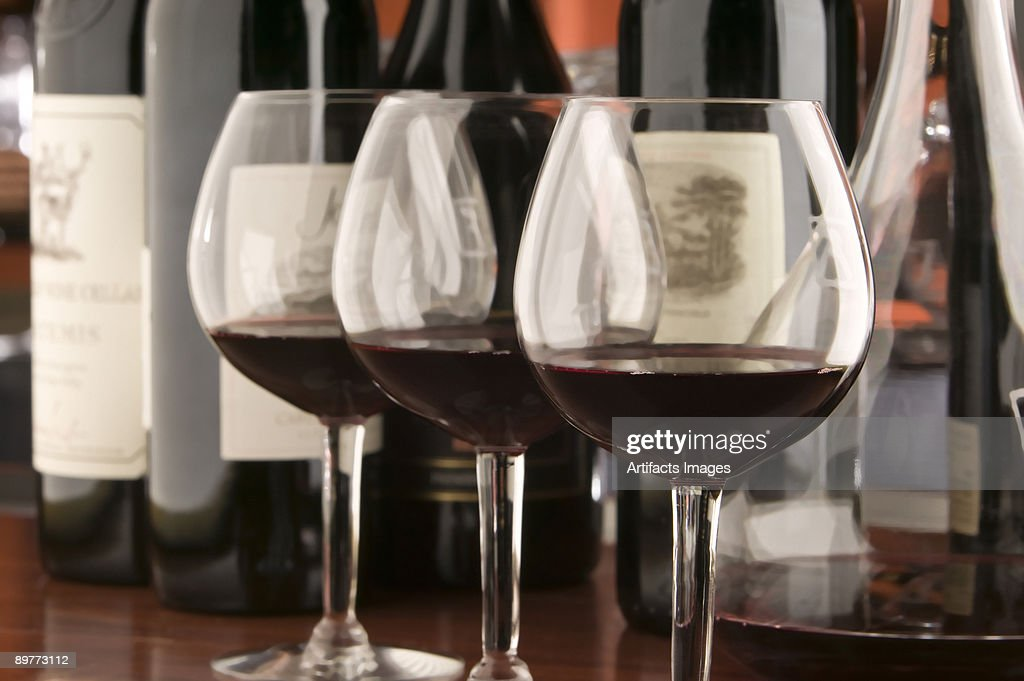 Three red wine glasses and bottles : Stock Photo