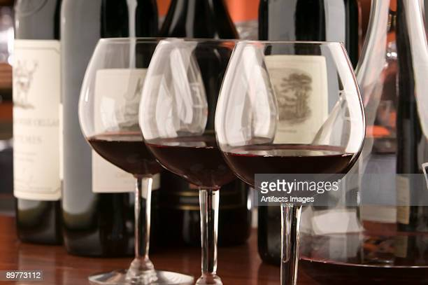 Three red wine glasses and bottles