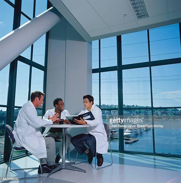 Three research scientists in lab coats meeting at round table