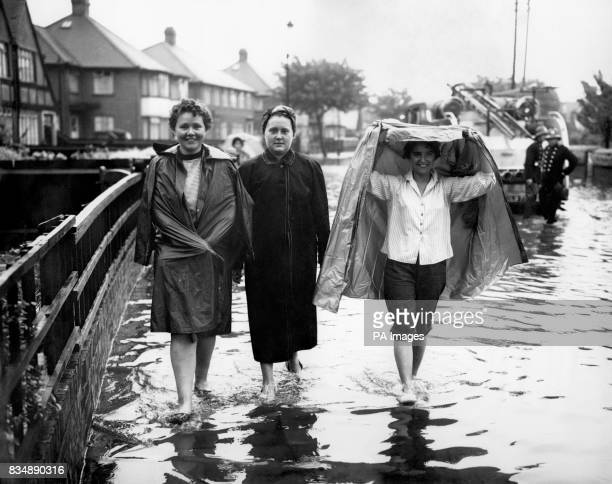 Three residents one of whom shelters against the rain walk through the flood water in Waterbank Road Catford south east London In places flood water...
