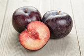 three ripe black plums on wood table, organic fruits