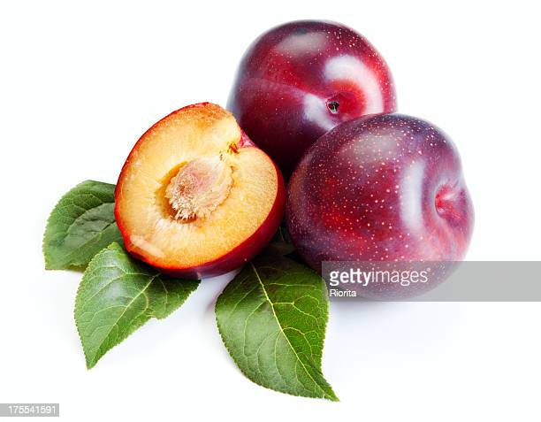 Three ripe plums on white background