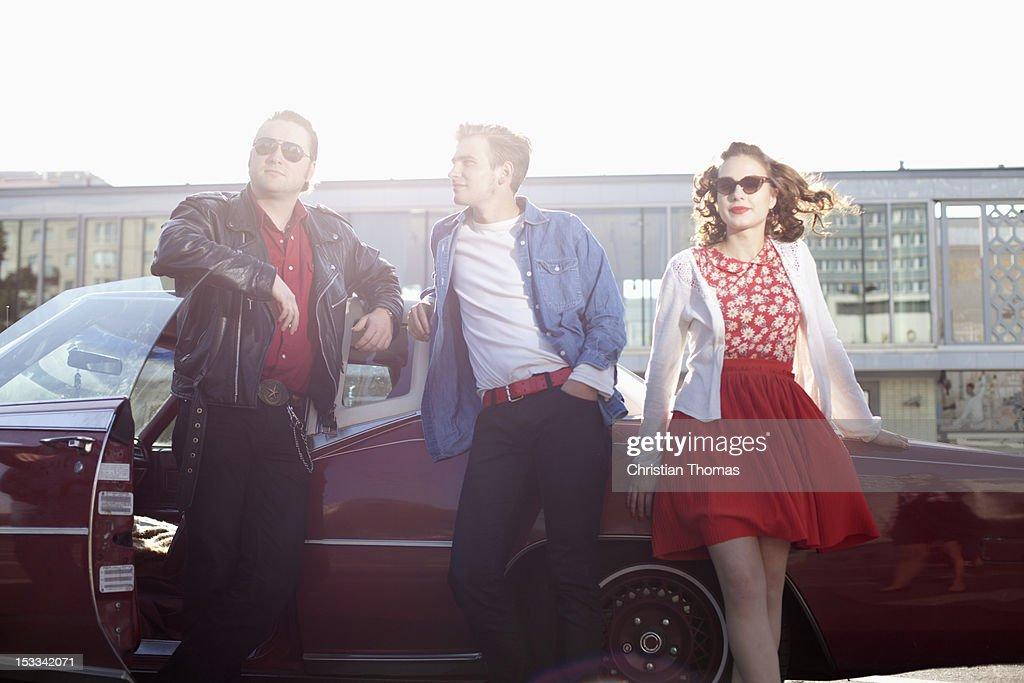 Three rockabilly friends leaning against a vintage car