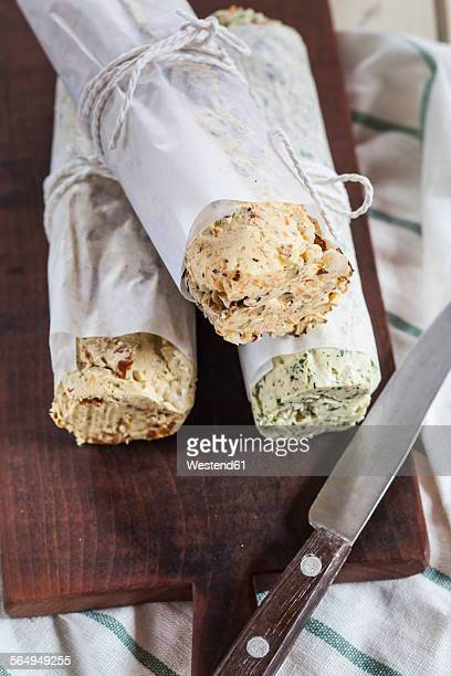 Three rolls of differently flavoured compound butters on chopping board
