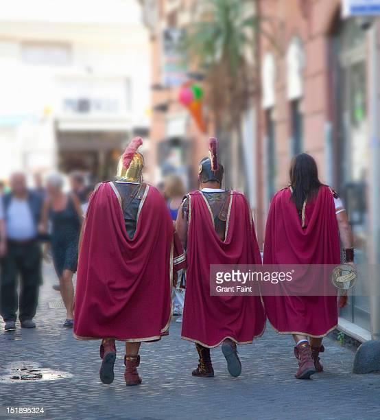 Three roman soldiers walking street.