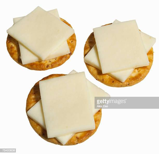 Three round crackers with sliced white cheese