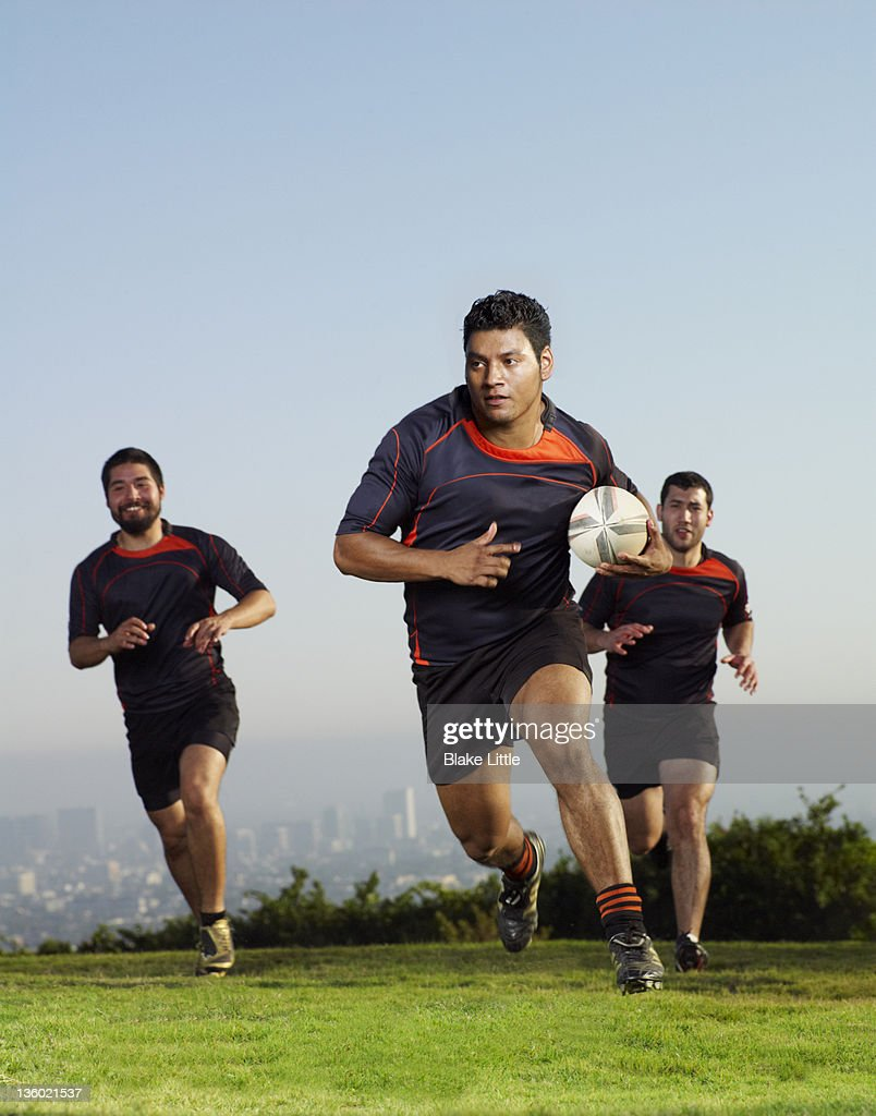 Three rugby players running on a field. : Stock Photo