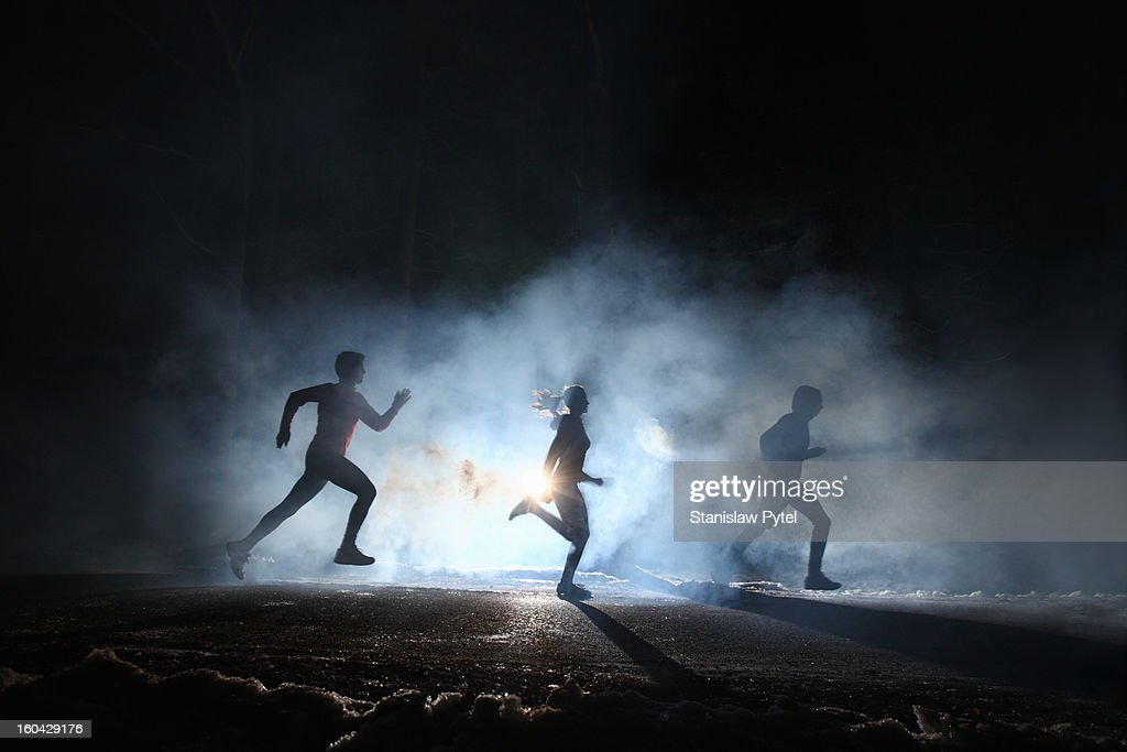 Three runners on foggy road at night : Stock Photo