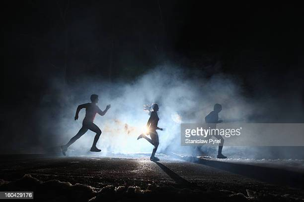 Three runners on foggy road at night