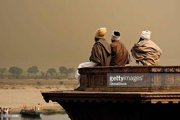 Three sadhus meditating by the Yamuna in Vrindavan