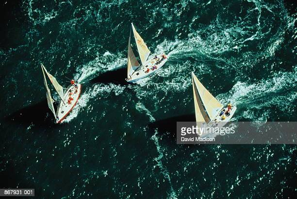 Three sailing boats competing in race, aerial view
