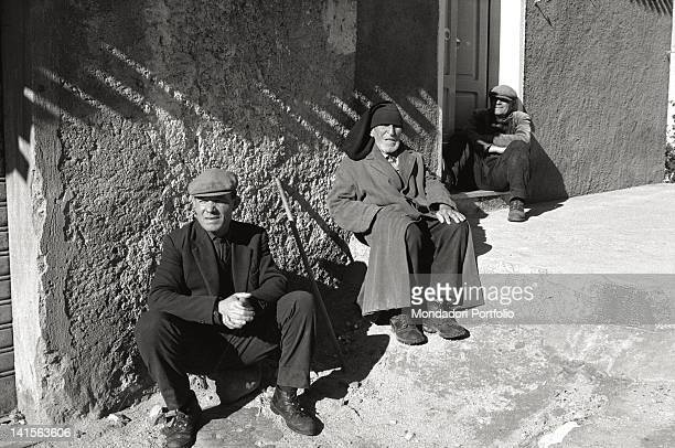 Three Sardinian shepherds are sat down on the road edge in a village in Barbagia in the province of Nuoro the eldest wears the typical beret the...