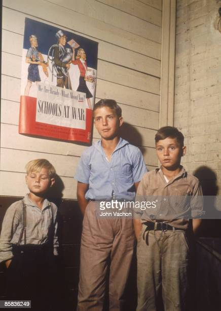 Three school boys with their hands in their pockets stand near a 'School at War' poster San Augustine County Texas April 1943