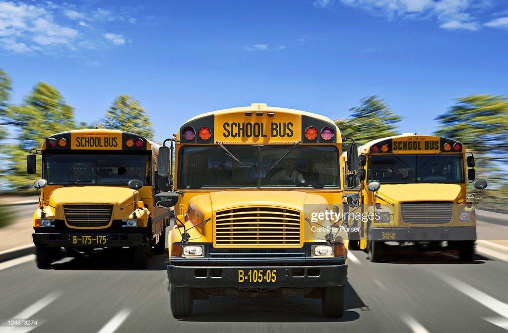 Three school buses driving towards camera : Stock Photo
