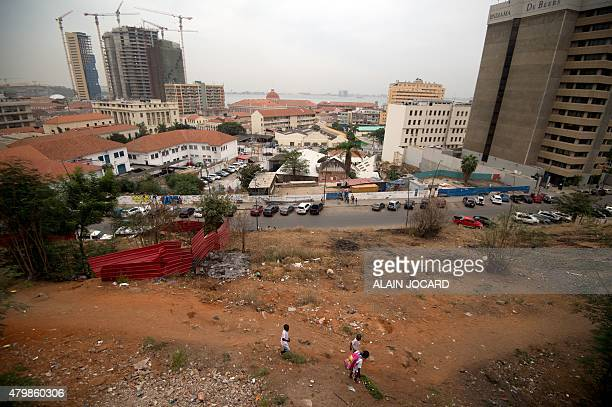 Three school children walk in Luanda on July 3 2015 AFP PHOTO/ ALAIN JOCARD