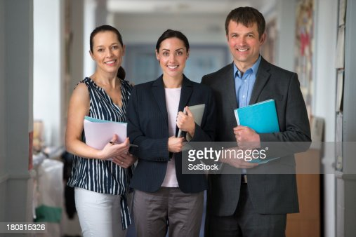 Three School Teachers Holding Paperwork And Smiling