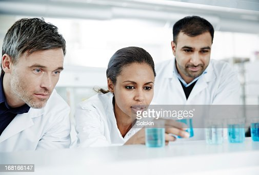 Three scientists examining glass beakers : Stock Photo