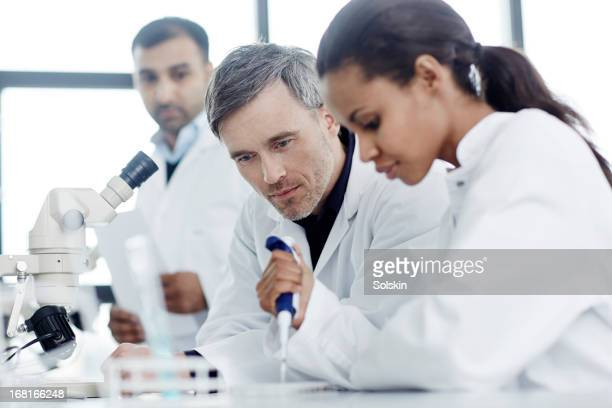 Three scientists examining samples in a laboratory