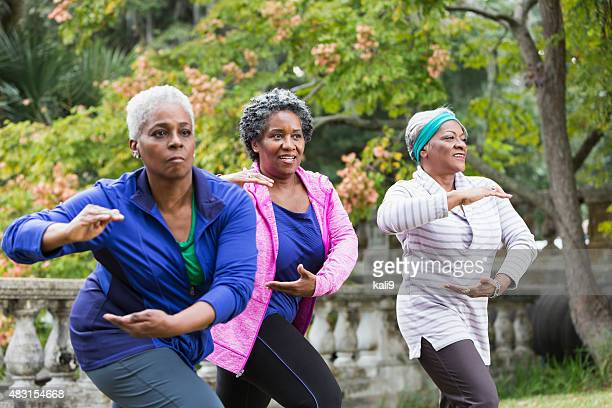 Three senior black women practicing Tai Chi