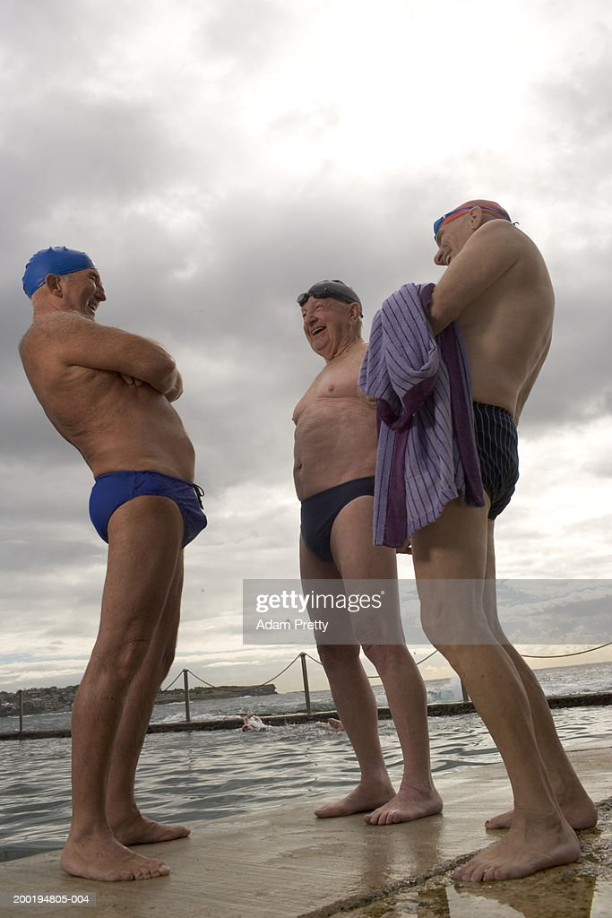 Three senior men at side of infinity pool, laughing, low angle view : Stock Photo
