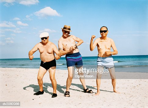 Three Senior Men in Swimming Trunks Stand on the Beach Flexing Their Muscles : 스톡 사진