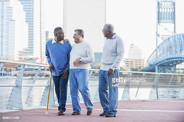Three senior men laughing, walking on city waterfront