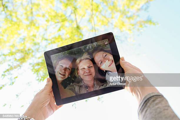 Three senior sisters taking a selfie from POV.