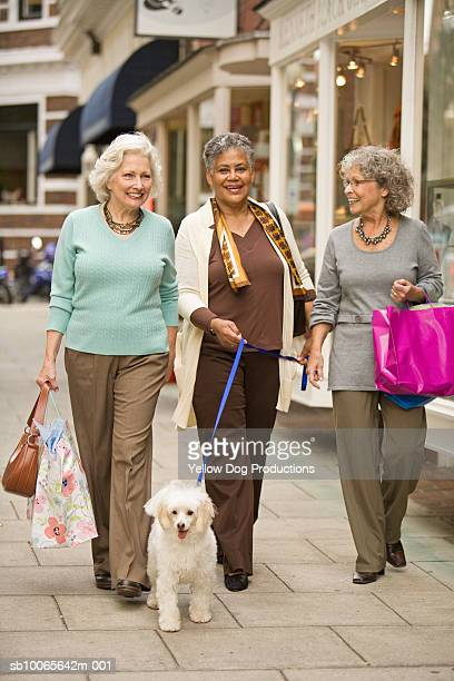 Three senior woman walking along street with shopping bags and dog on leash