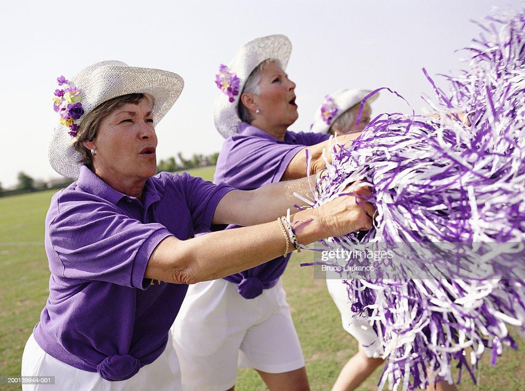Three senior women in cheerleading uniforms cheering, side view