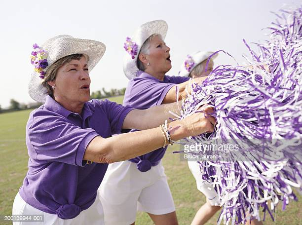 Three senior women in cheerleading uniforms cheering, side view