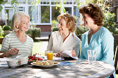 Three senior women in garden looking at holiday brochures, smiling