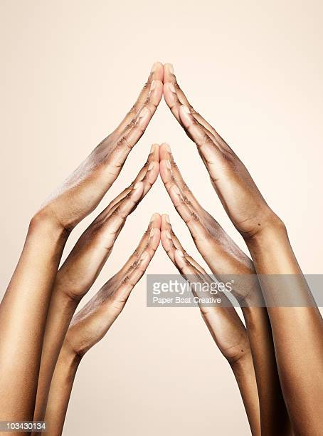 three sets of hands forming a house shape