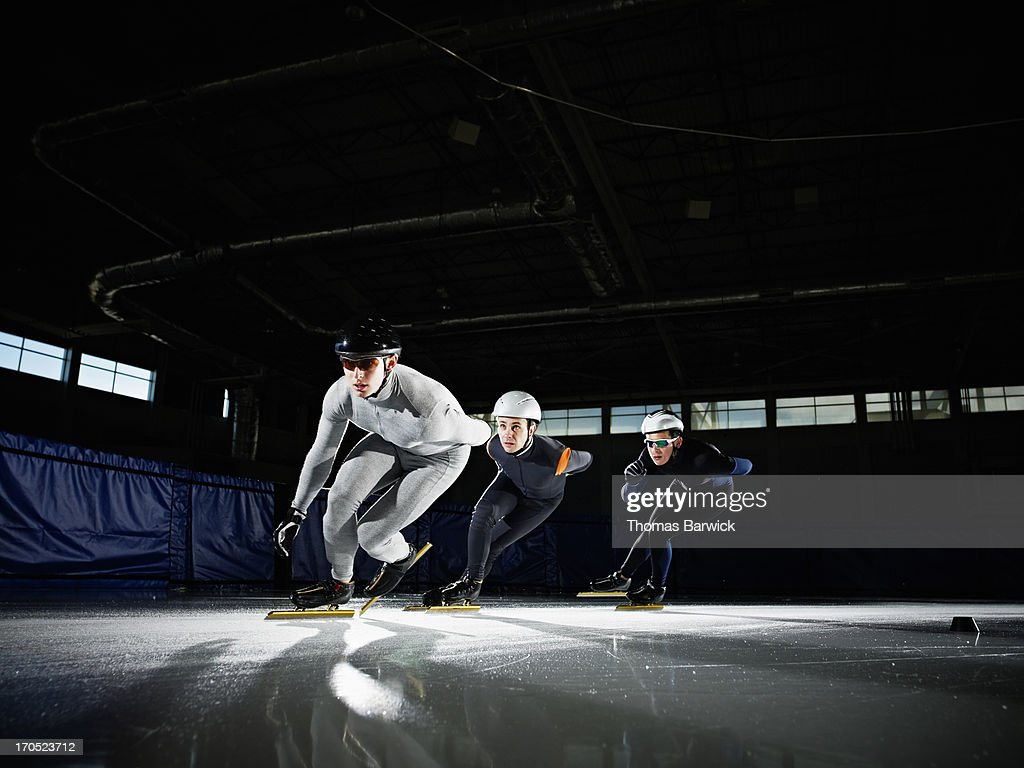 Three short track speed skaters racing around corn